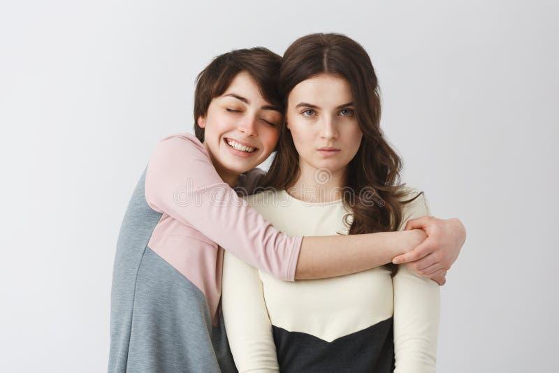 Ritratto della ragazza lesbica felice con i capelli di scarsità che abbracciano la sua amica scontrosa per la foto sul partito de fotografia stock libera da diritti