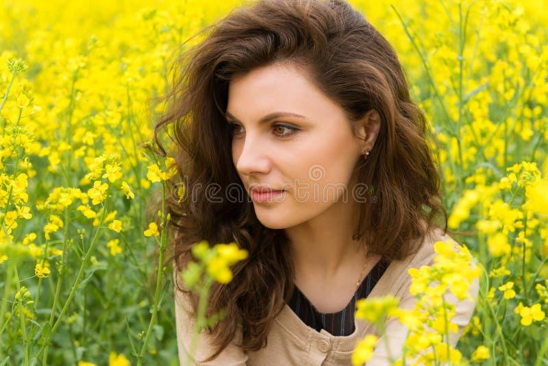 Ritratto della ragazza nel giacimento di fiore giallo fotografie stock
