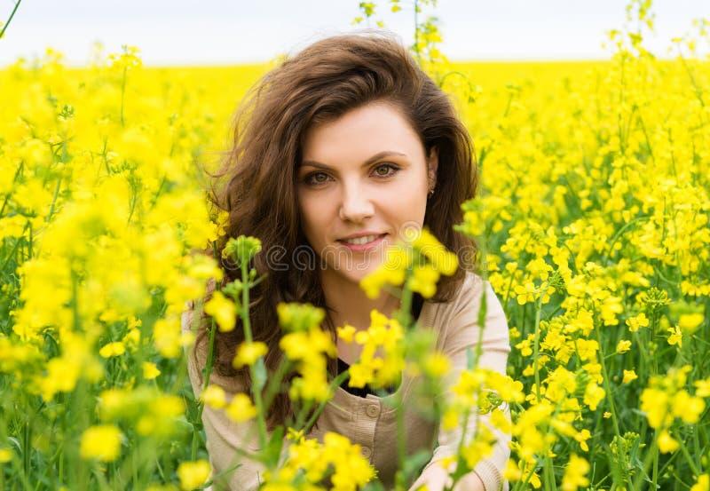 Ritratto della ragazza nel giacimento di fiore giallo immagini stock libere da diritti