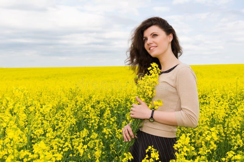 Ritratto della ragazza nel giacimento di fiore giallo fotografie stock libere da diritti