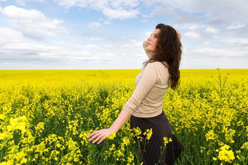 Ritratto della ragazza nel giacimento di fiore giallo fotografia stock