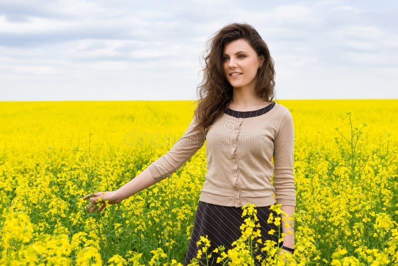 Ritratto della ragazza nel giacimento di fiore giallo immagine stock