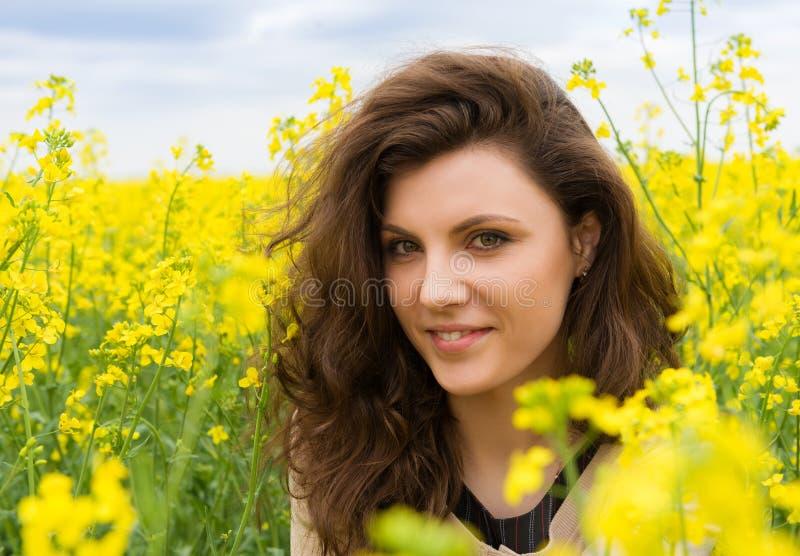 Ritratto della ragazza nel giacimento di fiore giallo fotografia stock libera da diritti
