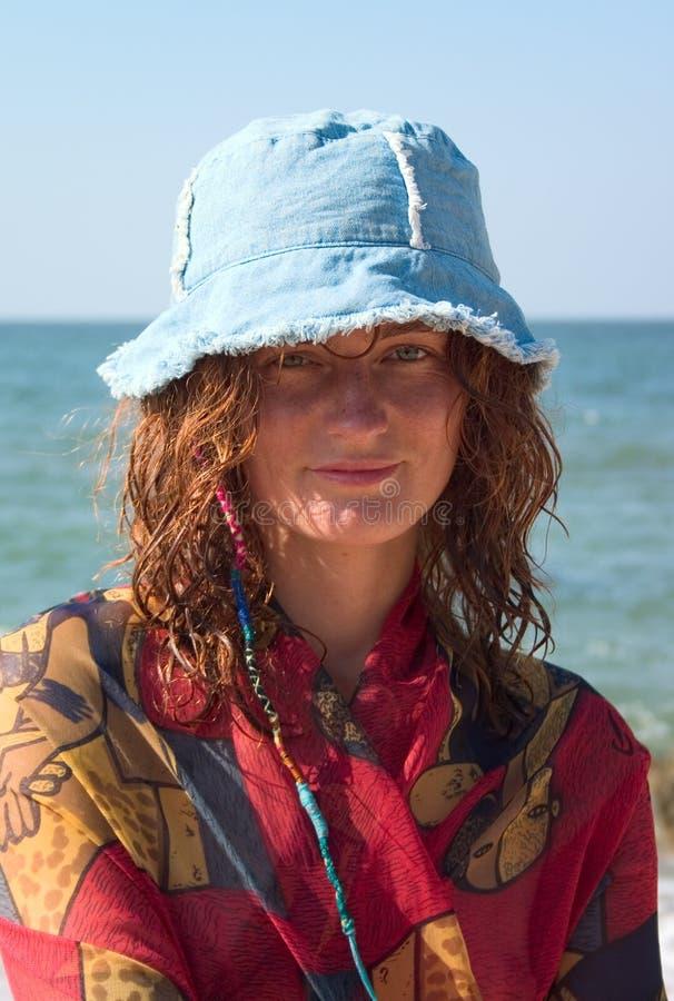 Ritratto della ragazza nel Panama blu alla spiaggia fotografia stock libera da diritti