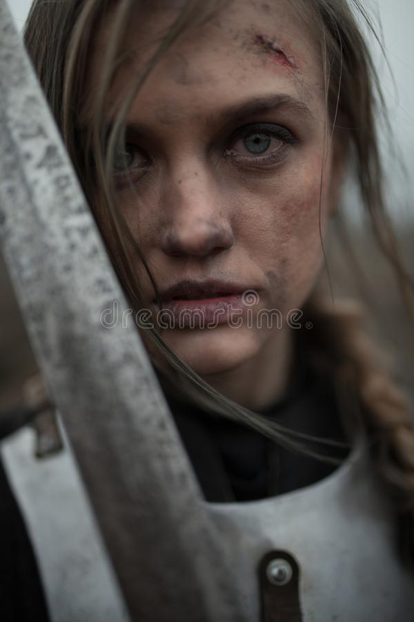 Ritratto della ragazza nell'immagine dell'arco del ` di Jeanne d in armatura e con la spada in sue mani fotografia stock