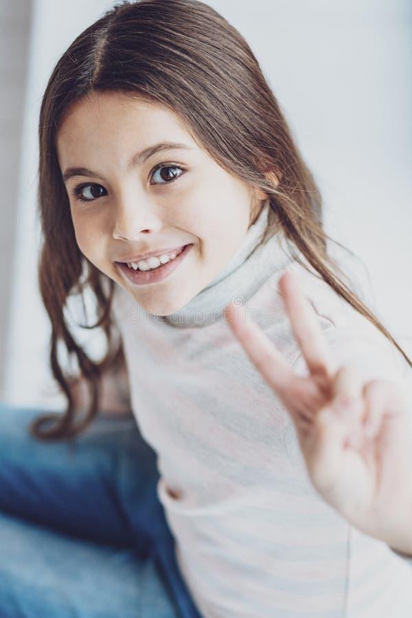 Ritratto della ragazza piacevole affascinante che mostra due dita fotografia stock libera da diritti
