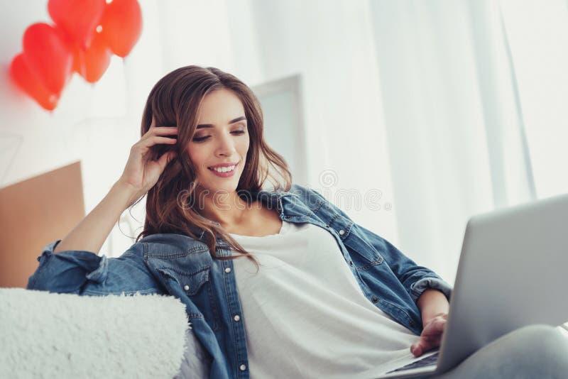 Ritratto della ragazza piacevole che per mezzo di un computer portatile immagini stock