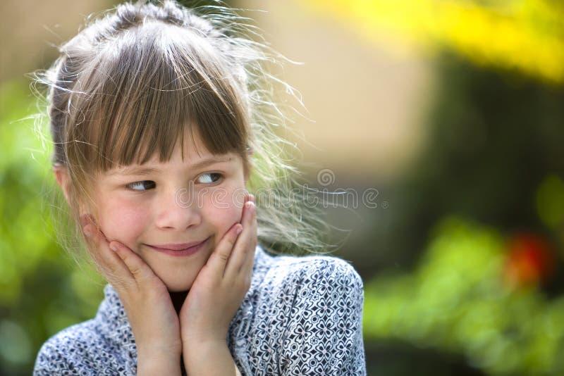 Ritratto della ragazza premurosa graziosa sveglia del bambino all'aperto su fondo luminoso variopinto soleggiato vago fotografia stock libera da diritti