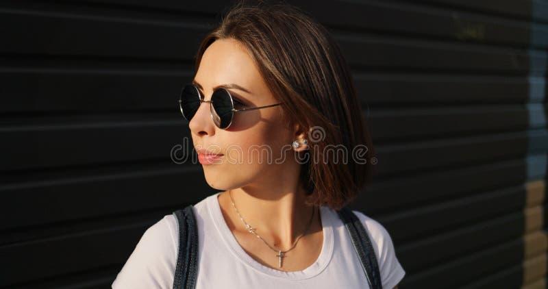 Ritratto della ragazza seria alla moda con i vetri che posano nella città immagine stock