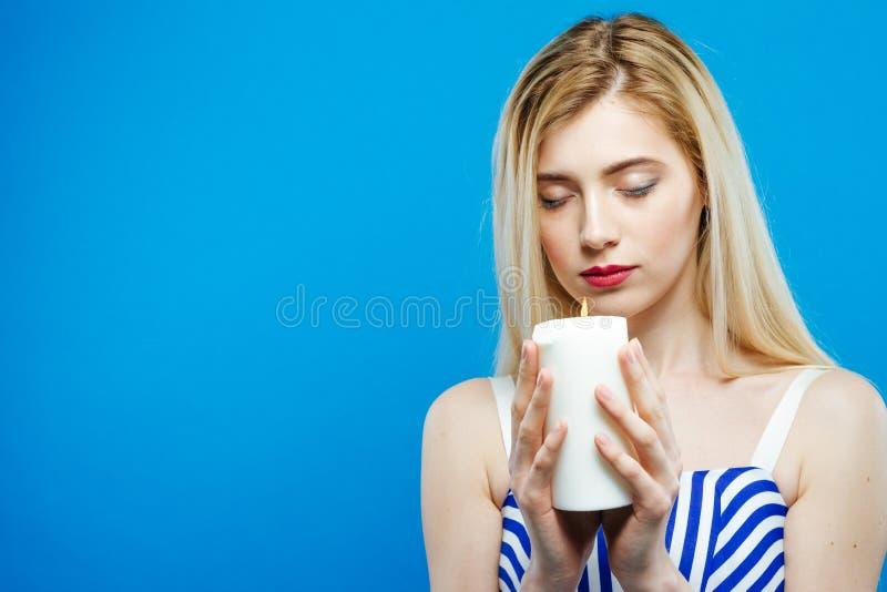 Ritratto della ragazza seria triste con gli occhi chiusi che tengono candela bianca in sue mani Bella bionda con le spalle nude fotografie stock