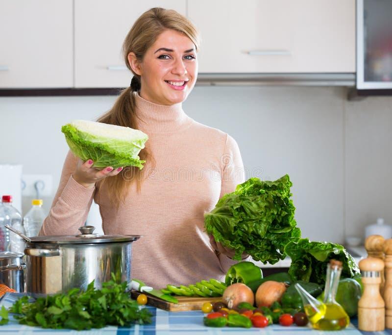 Ritratto della ragazza sorridente con lattuga all'interno immagini stock