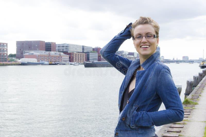 Ritratto della ragazza sorridente contro l'industriale e il backg del fiume immagine stock