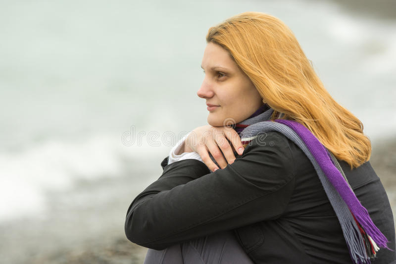 Ritratto della ragazza sorridente enigmatica su fondo della spuma un giorno freddo nuvoloso fotografia stock