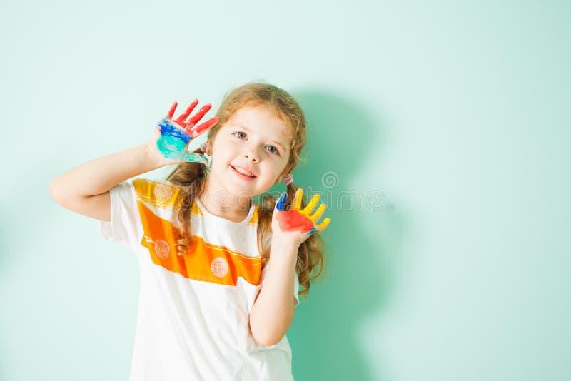 Ritratto della ragazza sorridente felice con le mani colorate fotografia stock