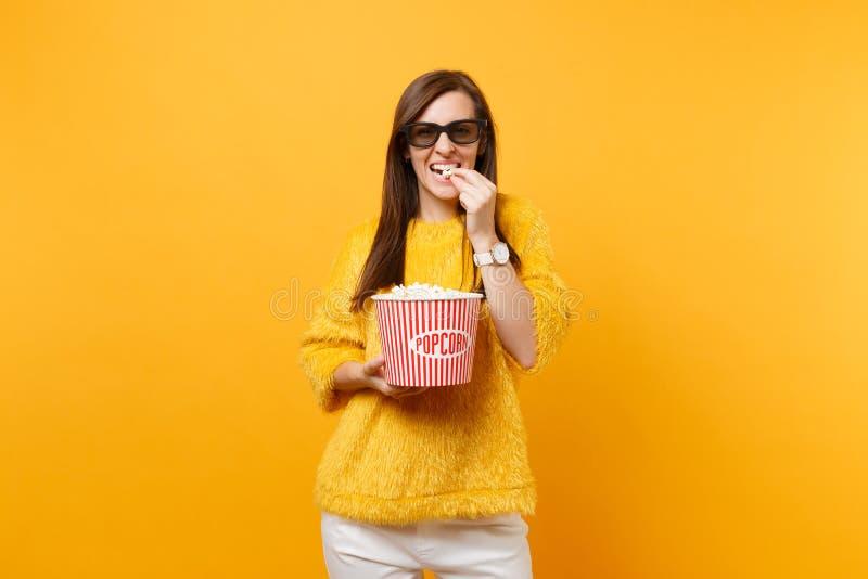 Ritratto della ragazza sorridente in vetri del imax 3d che guarda film, mangiante popcorn dal secchio isolato su luminoso immagine stock
