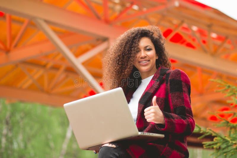Ritratto della ragazza splendida e sorridente che per mezzo del computer portatile nel luogo di lavoro fotografia stock
