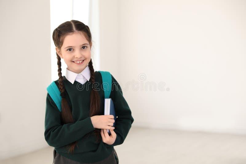 Ritratto della ragazza sveglia in uniforme scolastico con lo zaino ed il libro all'interno fotografia stock libera da diritti