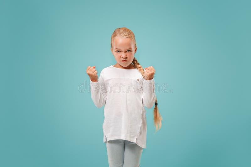 Ritratto della ragazza teenager arrabbiata su un fondo blu dello studio fotografie stock
