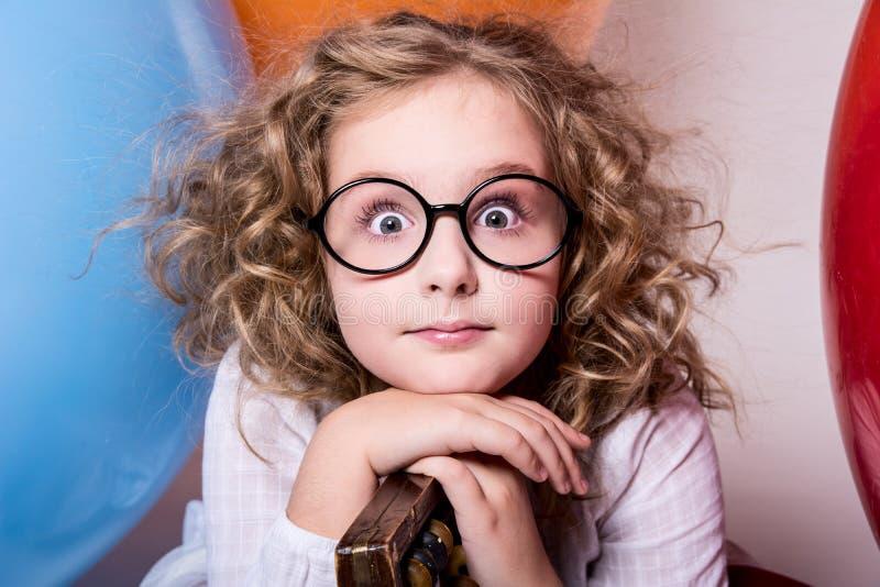 Ritratto della ragazza teenager riccia sorpresa in vetri sul backgrou immagini stock libere da diritti