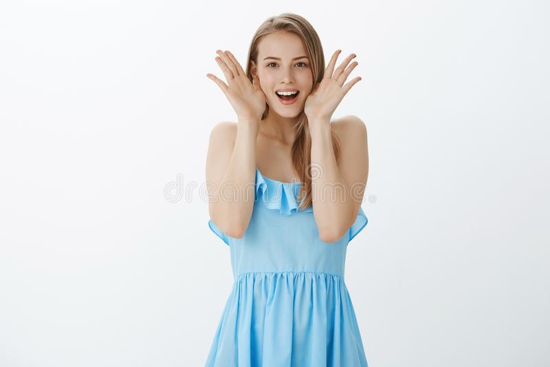 Ritratto della ragazza uscente carismatica ed allegra sorpresa con capelli giusti in abito da sera blu che decolla le palme dal f fotografia stock