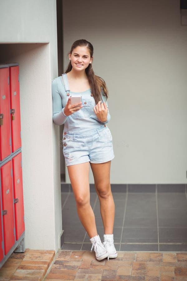 Ritratto della scolara che utilizza telefono cellulare nello spogliatoio fotografia stock libera da diritti