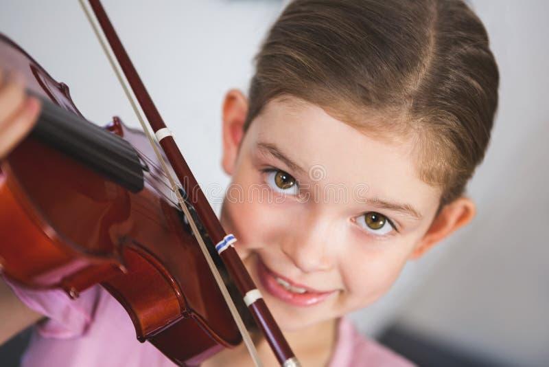 Ritratto della scolara sorridente che gioca violino in aula fotografia stock