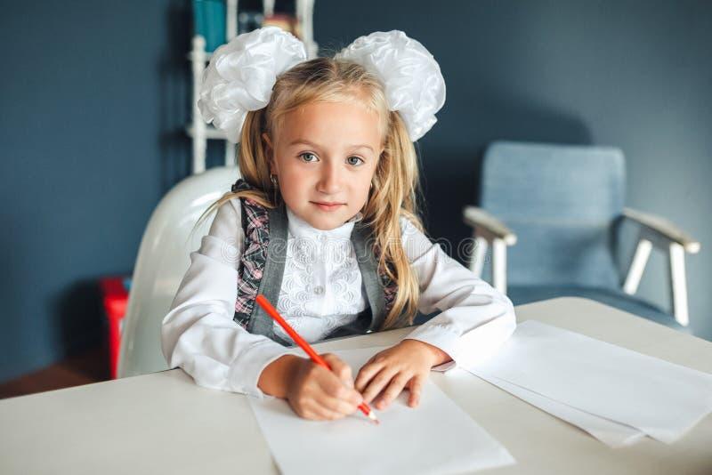 Ritratto della scolara sveglia che si siede e che disegna Bella ragazza nell'aula Piccolo scolara con gli archi bianchi che si si fotografia stock libera da diritti