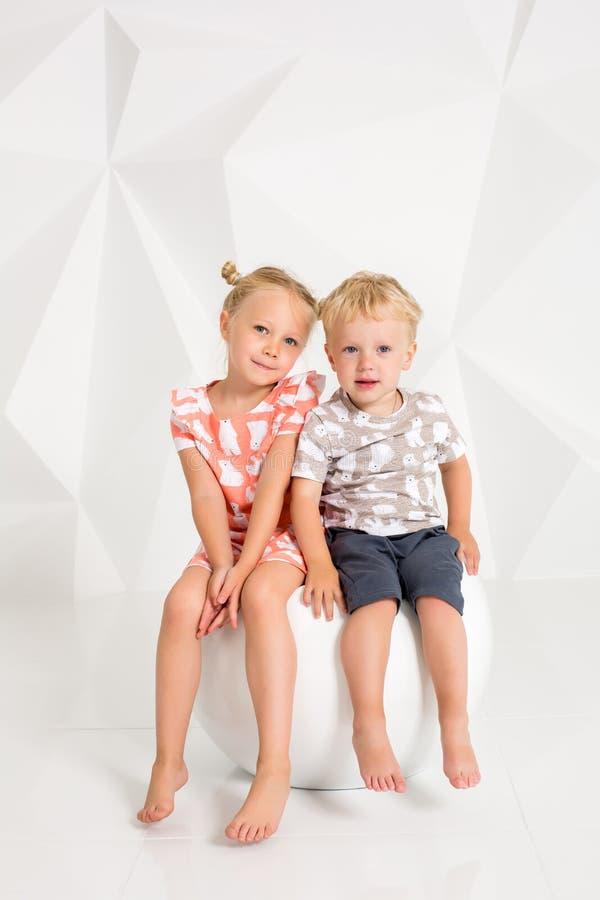 Ritratto della sorella e di suo fratello piccolo allo studio bianco fotografia stock
