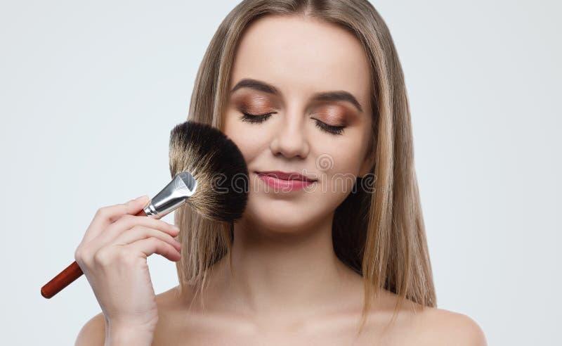 Ritratto della spazzola attraente della tenuta della giovane donna fotografia stock