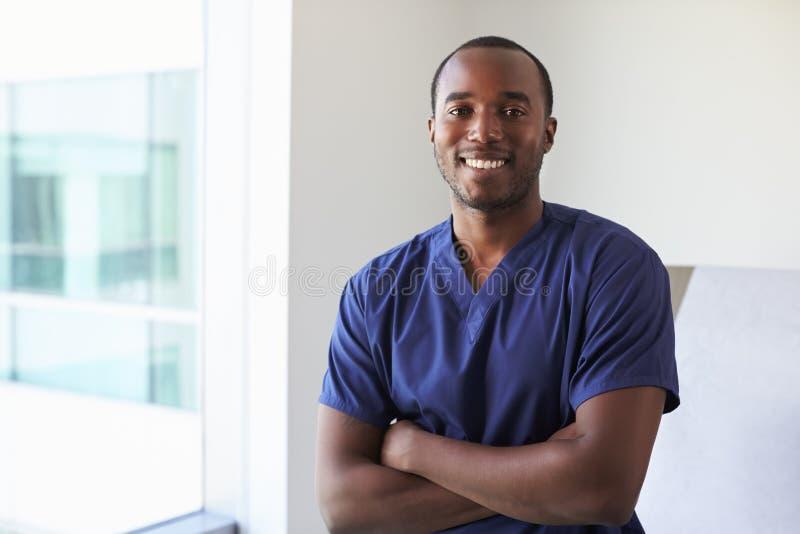 Ritratto della stanza maschio dell'esame di Wearing Scrubs In dell'infermiere fotografie stock libere da diritti