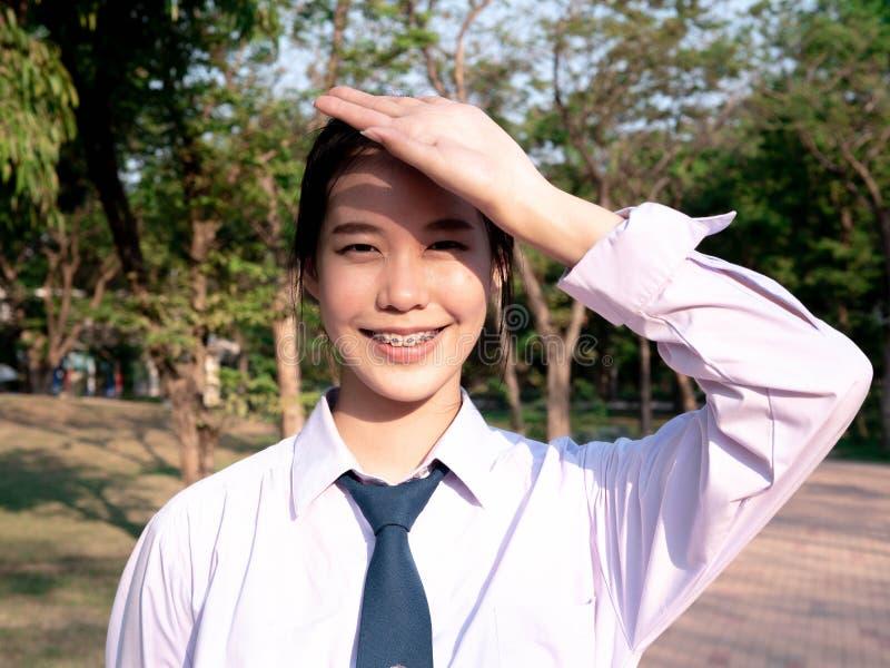 Ritratto della studentessa asiatica nello stile della Tailandia dell'uniforme scolastico e di sorridere con il giorno ventoso e s fotografia stock