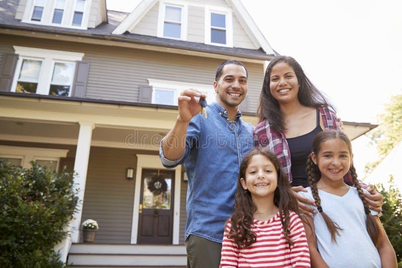 Ritratto delle chiavi della tenuta della famiglia alla nuova casa sul muoversi nel giorno immagine stock