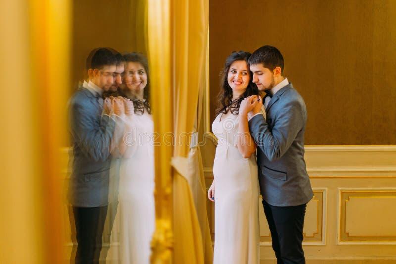 Ritratto delle coppie affascinanti della persona appena sposata nell'interno lussuoso con la riflessione di paia in grande specch immagine stock