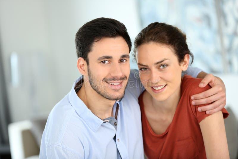 Ritratto delle coppie amorose a casa che abbracciano fotografia stock