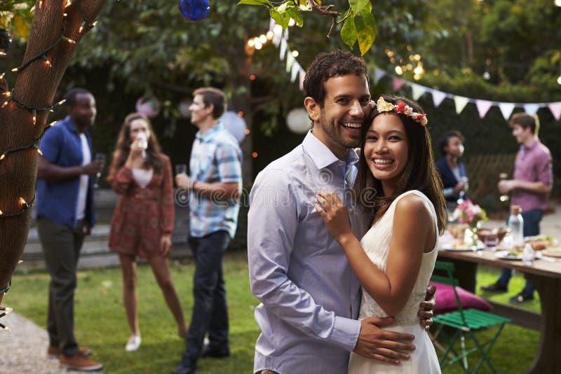 Ritratto delle coppie che celebrano nozze con il partito del cortile fotografia stock libera da diritti