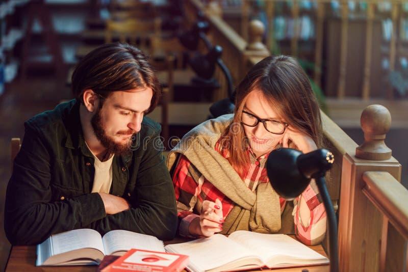 Ritratto delle coppie degli studenti in biblioteca immagini stock libere da diritti