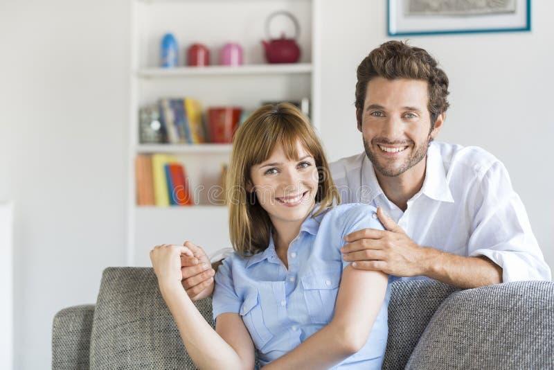 Ritratto delle coppie di trenta anni allegre che si siedono sul sofà in casa moderna fotografia stock
