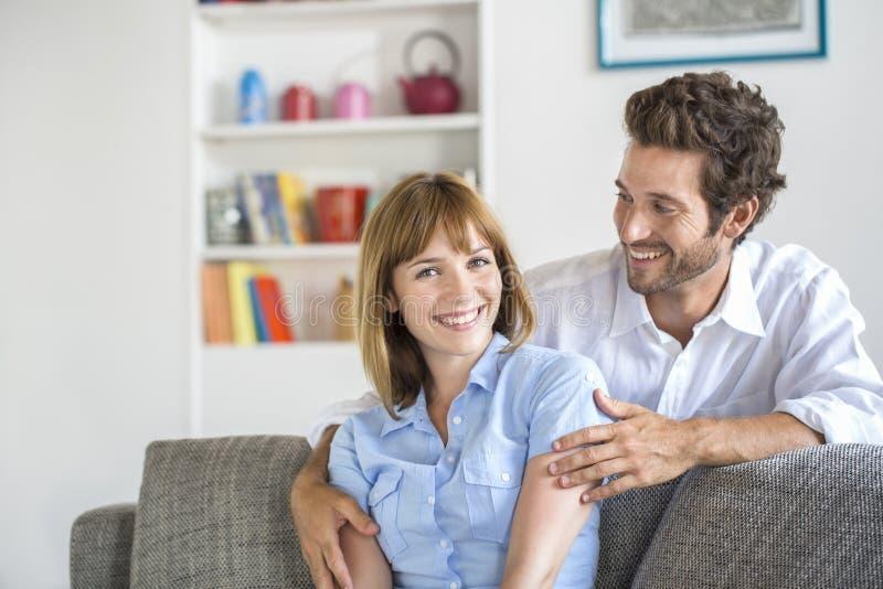 Ritratto delle coppie di trenta anni allegre che si siedono sul sofà nella m. fotografie stock libere da diritti