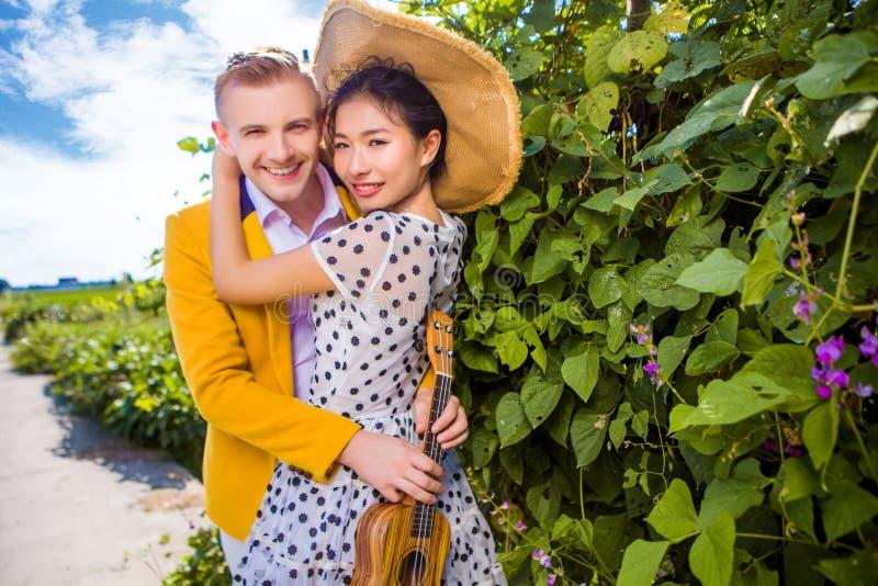 Ritratto delle coppie felici che abbracciano dalle piante fotografia stock