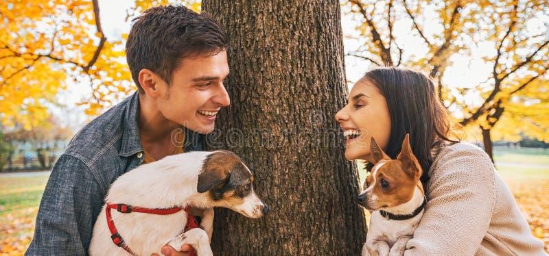Ritratto delle coppie felici con i cani all'aperto nel parco di autunno fotografia stock libera da diritti