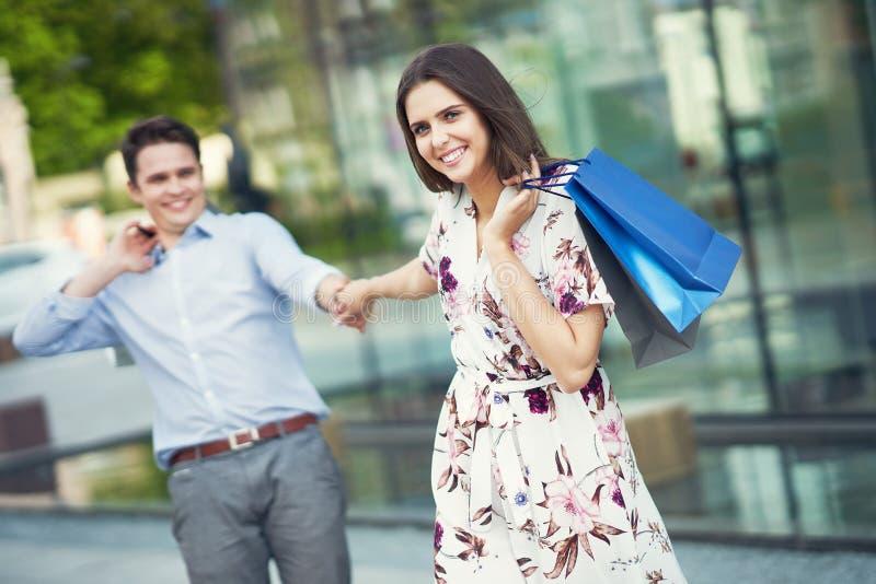 Ritratto delle coppie felici con i sacchetti della spesa in citt? che sorride e che huging fotografie stock libere da diritti
