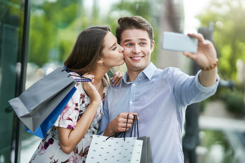 Ritratto delle coppie felici con i sacchetti della spesa in citt? che sorride e che huging fotografia stock