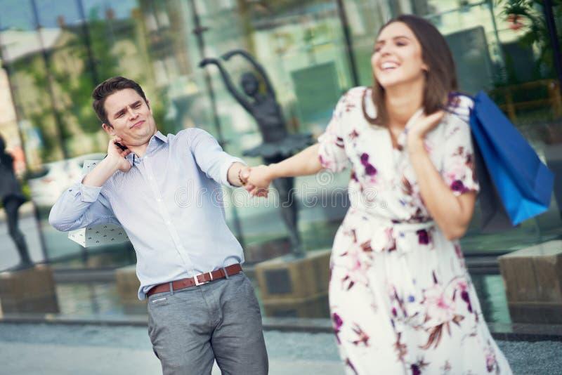 Ritratto delle coppie felici con i sacchetti della spesa in citt? che sorride e che huging immagine stock