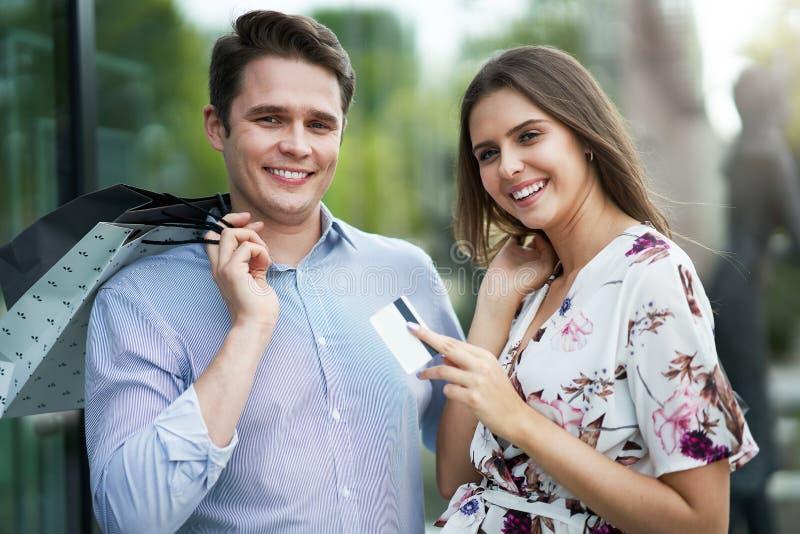 Ritratto delle coppie felici con i sacchetti della spesa in citt? che sorride e che huging immagini stock
