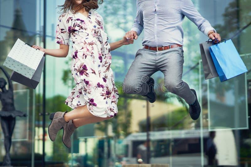 Ritratto delle coppie felici con i sacchetti della spesa in citt? che sorride e che huging immagini stock libere da diritti