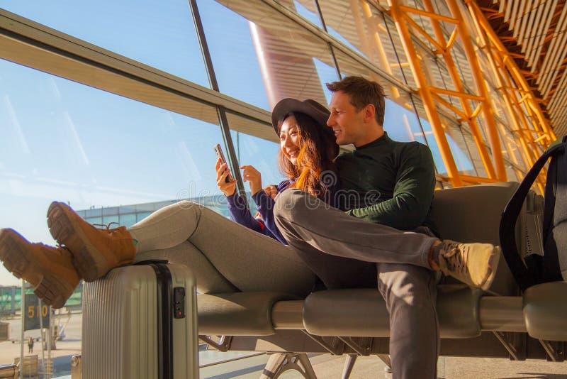 Ritratto delle coppie felici facendo uso del telefono cellulare all'aeroporto fotografia stock libera da diritti