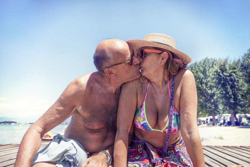 Ritratto delle coppie mature moderne che baciano in costume da