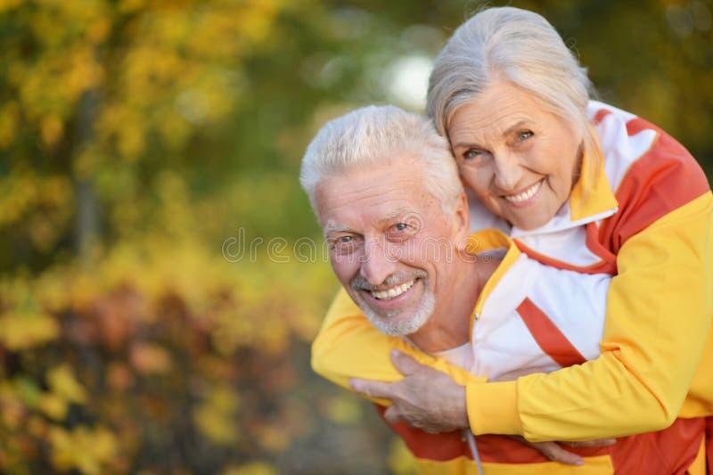 Ritratto delle coppie senior adatte felici nel parco di autunno immagini stock