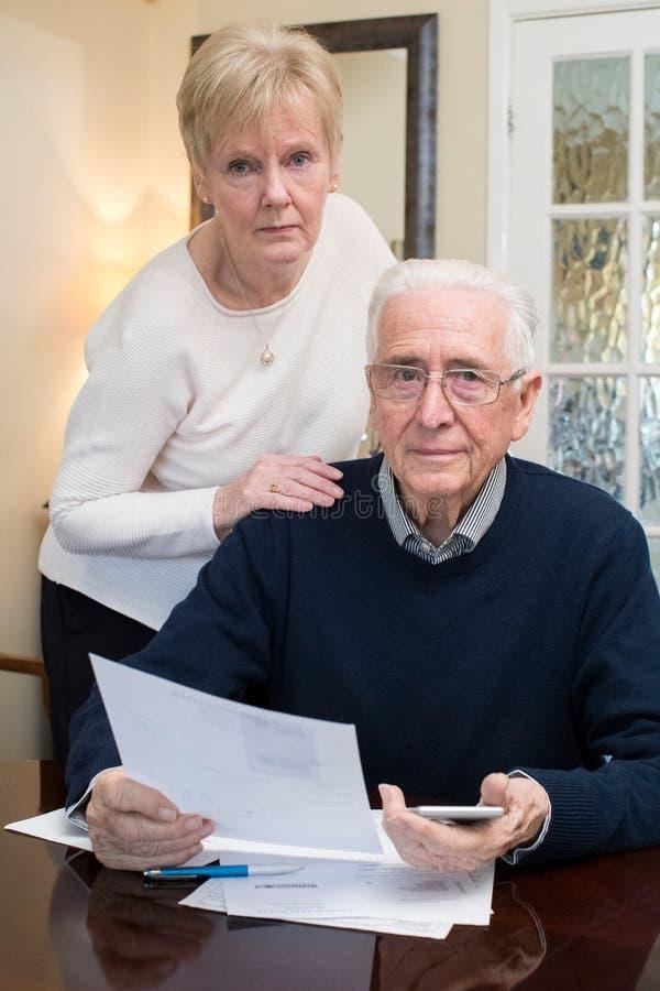 Ritratto delle coppie senior interessate che esaminano le finanze domestiche fotografie stock