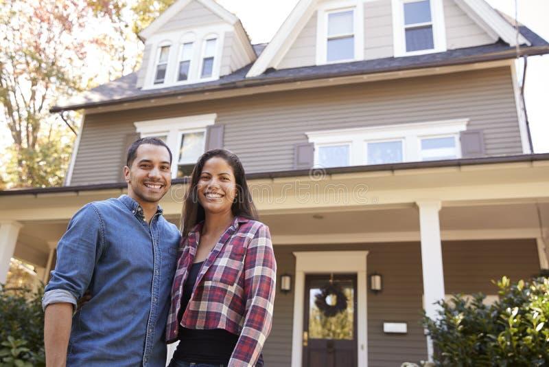Ritratto delle coppie sorridenti che stanno in Front Of Their Home immagini stock
